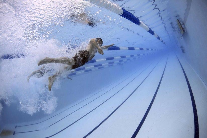 Un homme nage dans une piscine publique. On voit les lignes noires dans le fond de la piscine .