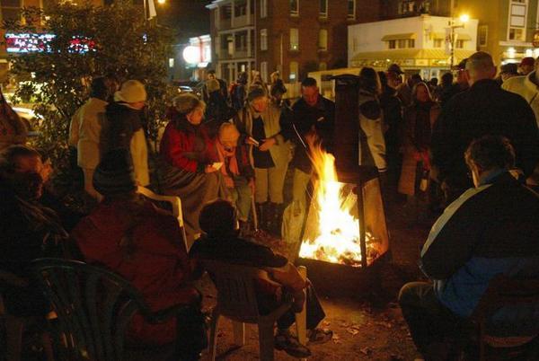 Groupe de personnes sans abris autour d'un feu.