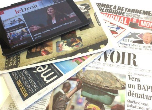 Quelques journaux papier et une tablette numérique.
