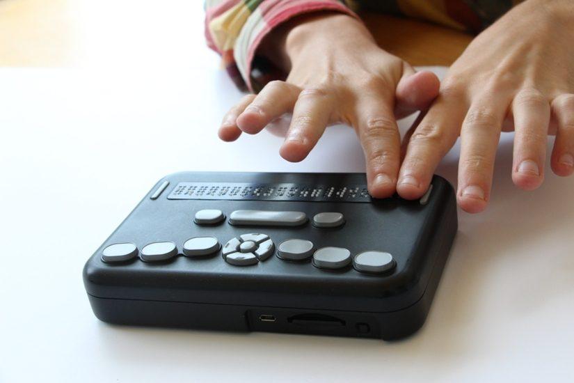 On voit des mains utiliser un lecteur braille Orbit.