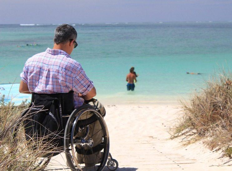 Homme en fauteuil roulant sur une plage près de la mer.