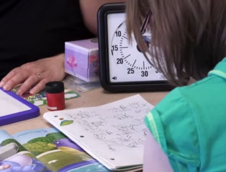 Jeune fille travaillant dans un cahier, à côté d'une minuterie.