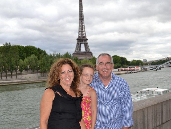 Sophie Boisvert, son conjoint et Arielle posent devant la tour Eiffel.