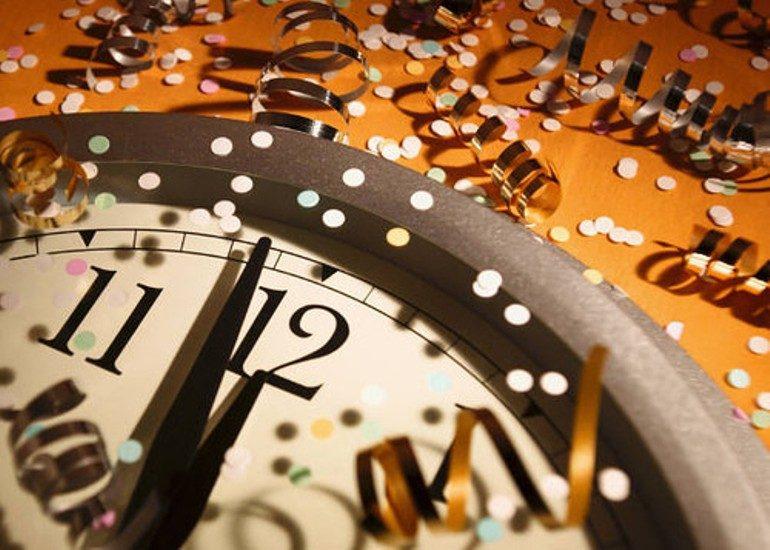 Horloge indiquant minuit moins une, avec rubans et confettis.