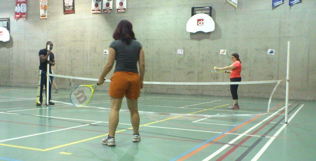 Deux personnes non-voyantes jouent au tennis dans un gymnase. ASAQ