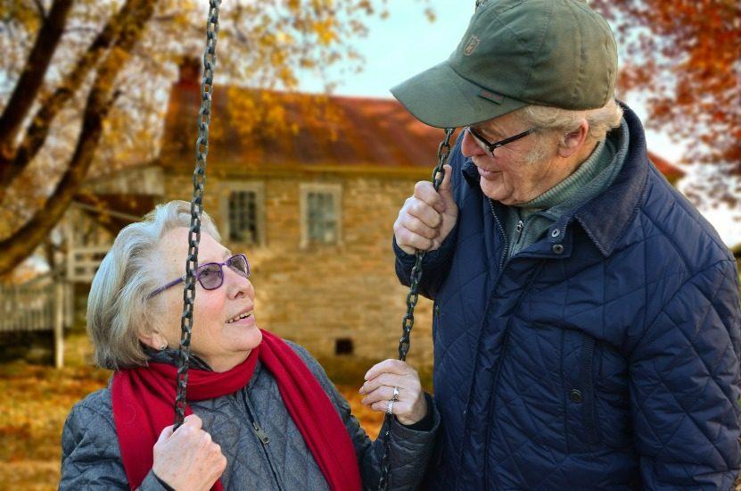 Un homme âgé regarde amoureusement une dame âgée assise sur une balançoire.