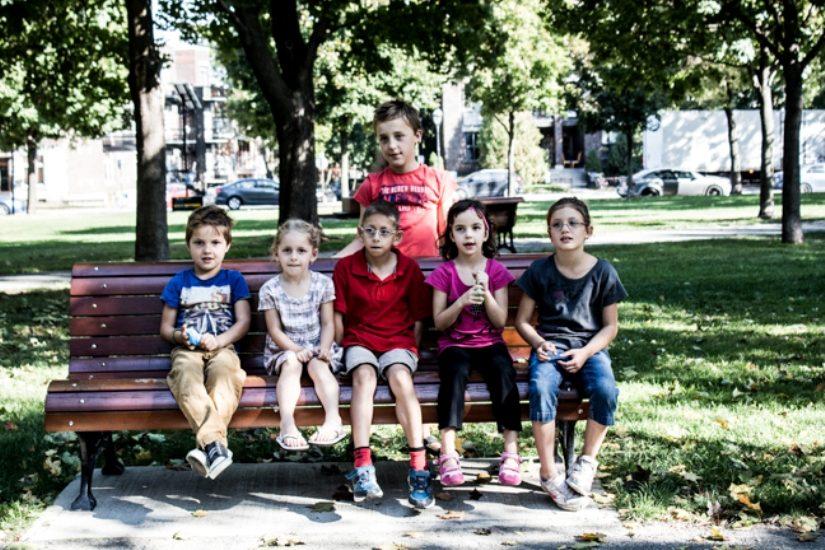 Groupe d'enfants assis sur un banc pour un tournage de l'AQEPA.