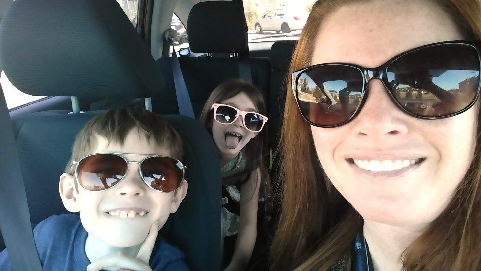 Katherine Bourdon et ses enfants posent en voiture avec des verres fumés.