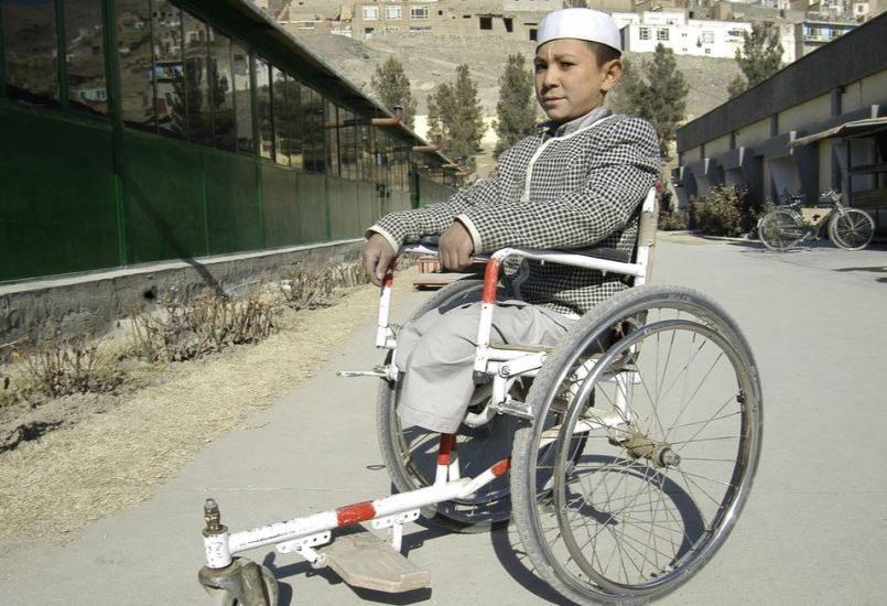 Un jeune garçon amputé en fauteuil roulant dans une rue de Kaboul.