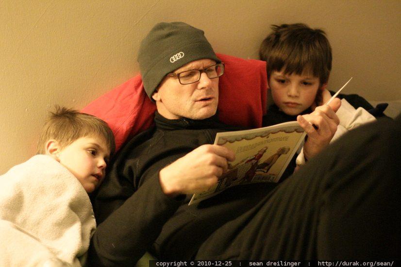 Un papa et ses deux garçons lisent une histoire au lit. Les deux petits semblent captivés.