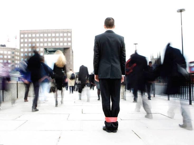 Des gens se rendent au travail. Un homme semble ne peut les suivre car ses jambes sont attachées par un ruban rouge.
