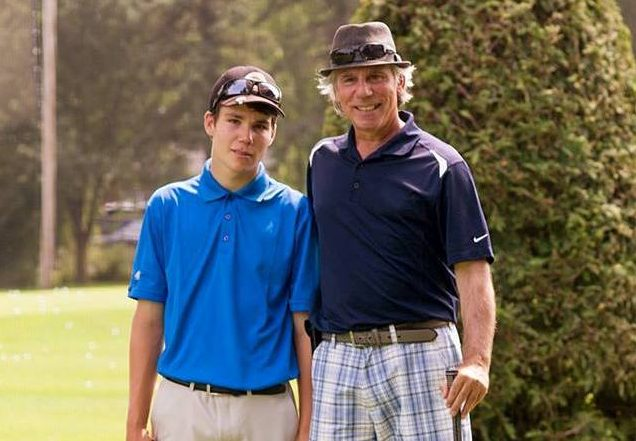 Charles et Paul St-Germain posent sur un terrain de golf, bâtons à la main.