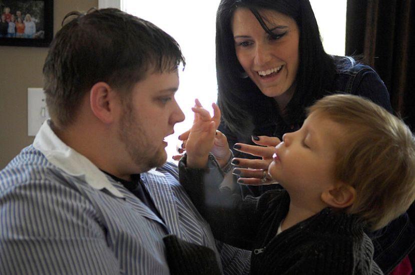 Un garçonnet blond touche le nez de son père sous le regard amusé de sa mère.