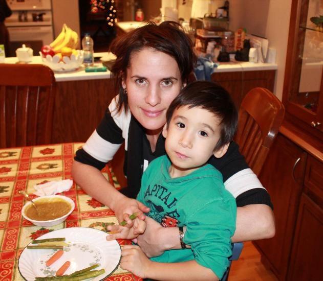Jennifer Mallin et son fils Adami posent à table devant un bol de soupe et des crudités.