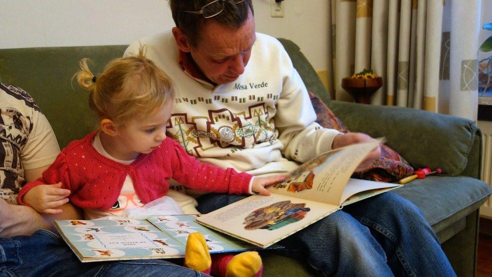 Une petite fille blonde lit avec son père ou son grand père.