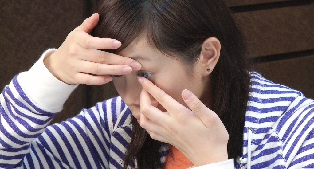 Une dame est en train de mettre une lentille cornéenne.