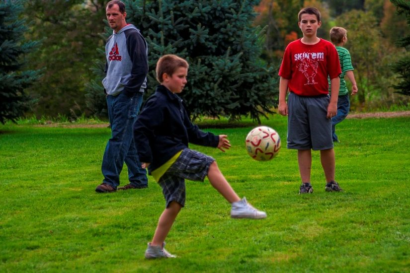 Des enfants s'amusent avec un ballon de soccer.