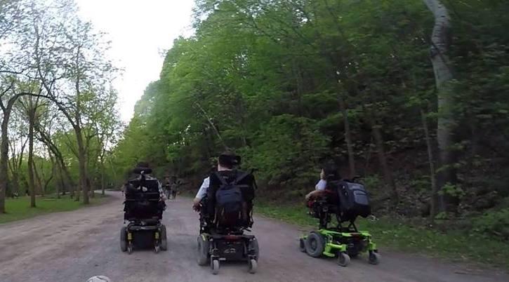 Trois personnes en fauteuil roulant motorisé se promenant sur le Mont-Royal.