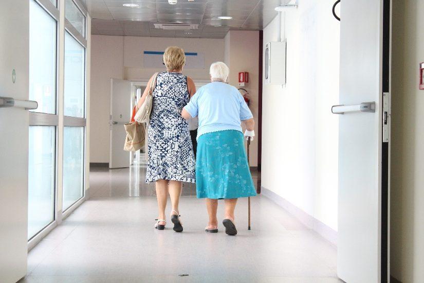 On voir deux dames de dos, dont une âgée qui marche avec une canne, dans un couloir d'hôpital.