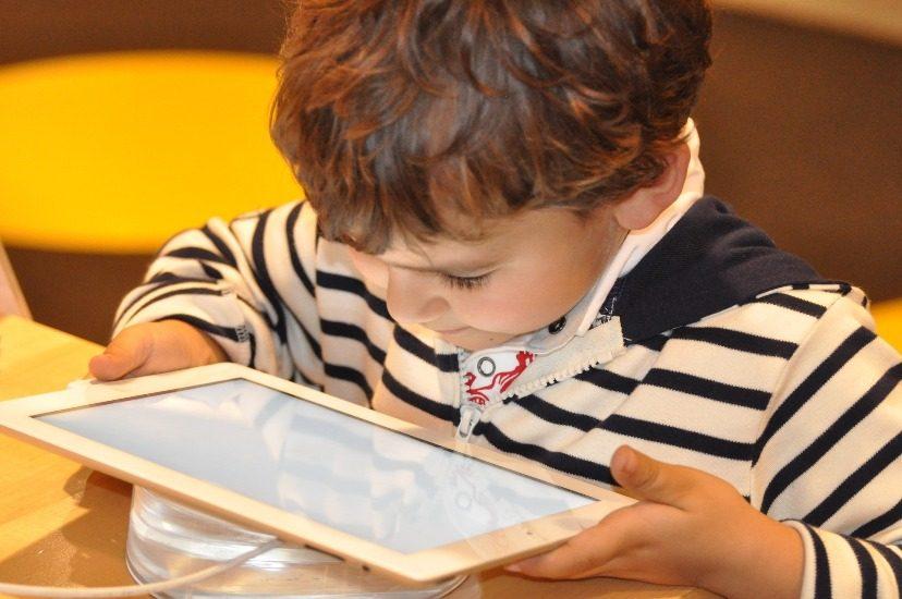 Petit garçon qui regarde une tablette de très près.