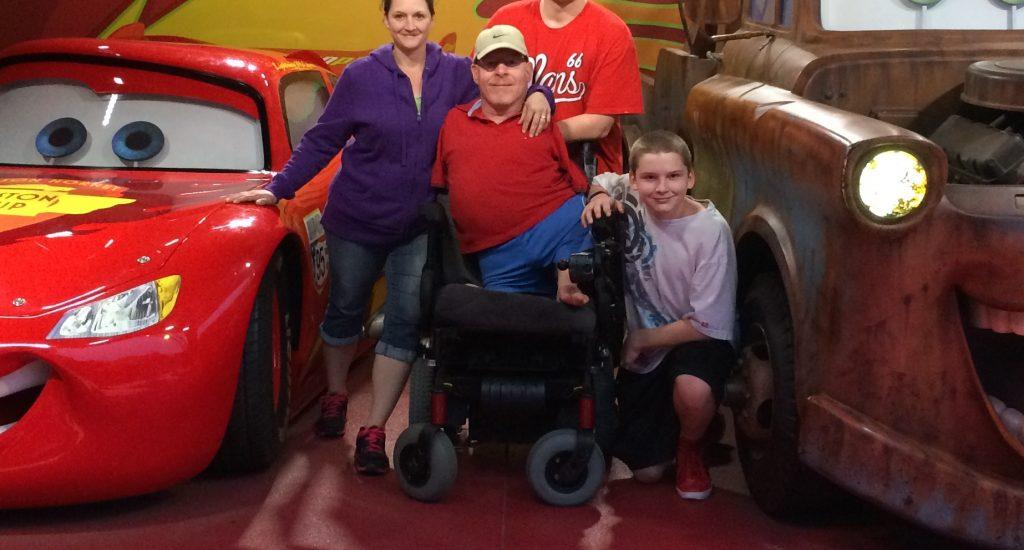 Jacques Théberge avec sa femme et ses deux grands fils posent devant des voitures du file Cars à  Disney.