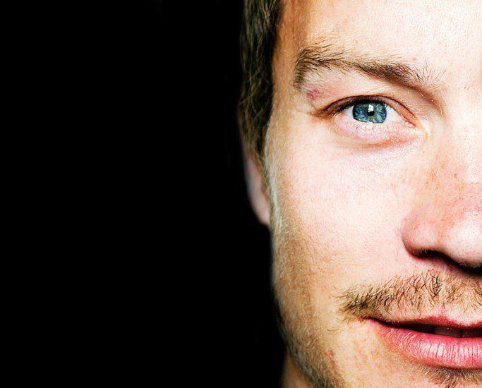 Gros plan sur la moitié du visage d'un homme aux yeux bleus.