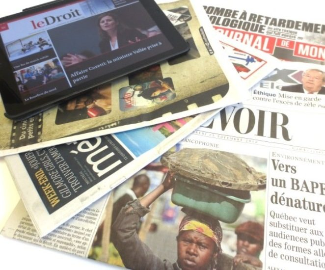 Des quotidiens papiers et une tablette électronique.