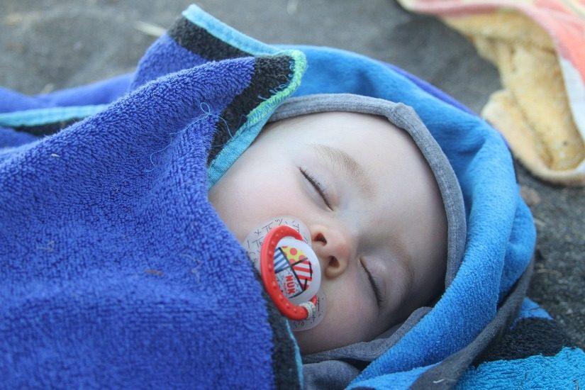 Nourrisson enveloppé dans une serviette. Il dort.