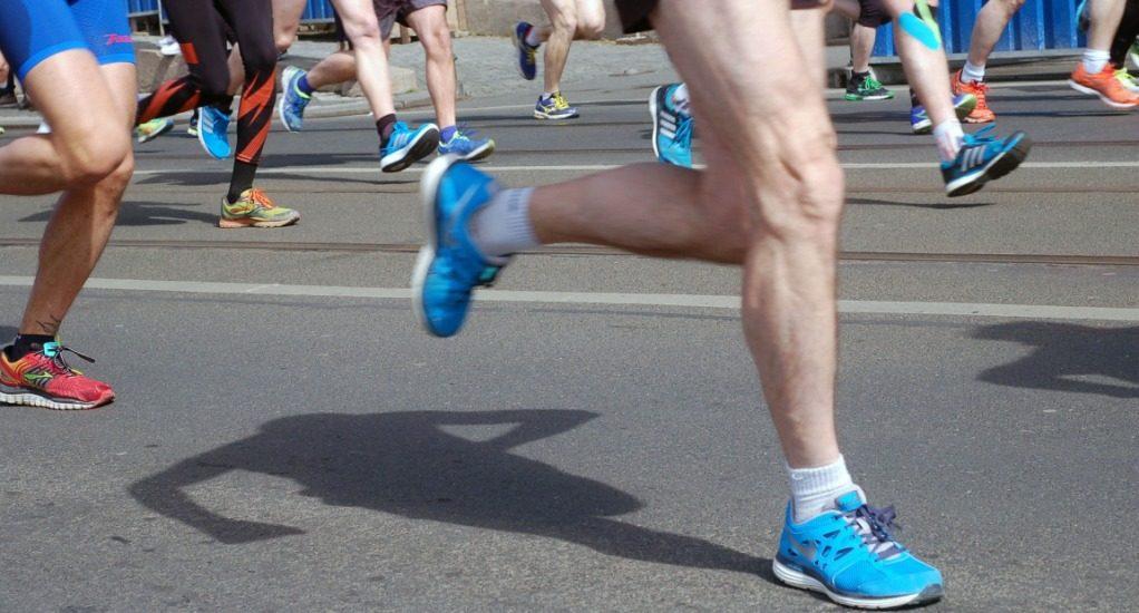 Jambes et pieds de marathoniens qui courent sur l'asphalte.