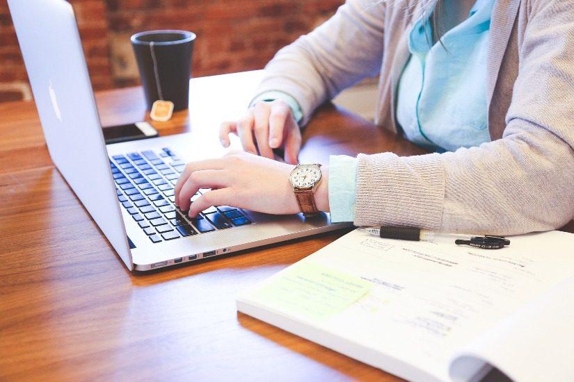 Une personne travaille sur un ordinateur portable avec un manuel scolaire juste à côté d'elle.