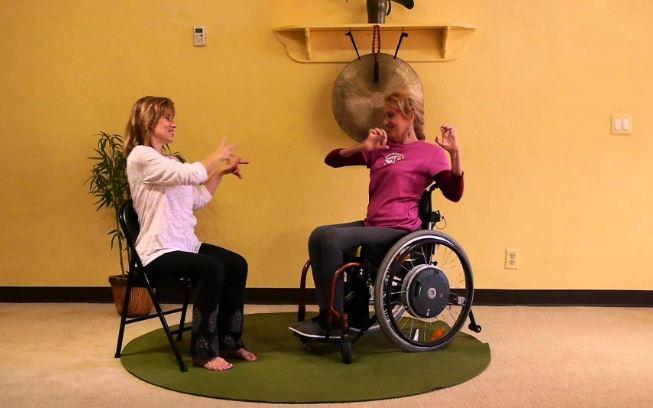Deux femmes assises font du yoga. Une d'entre elles est en fauteuil roulant.