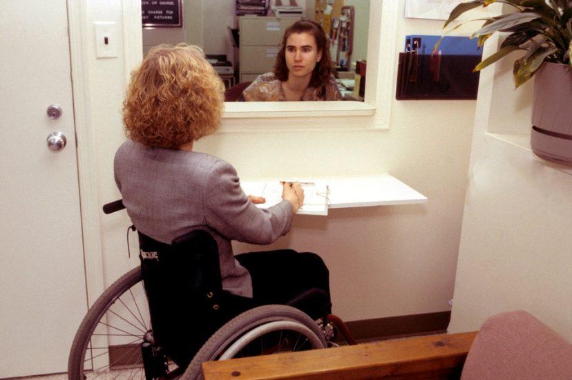 Dans un bureau de type médical, une dame en photo roulant prend des notes en s'adressant à la réceptionniste.
