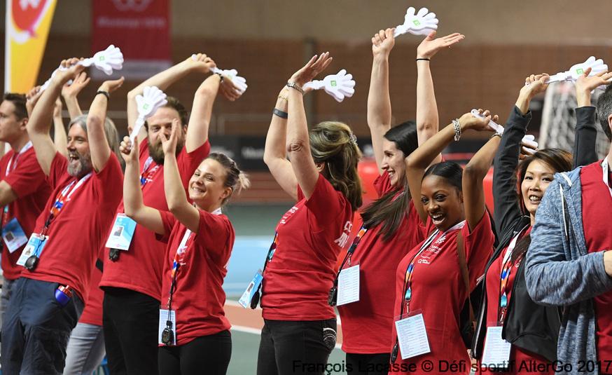 Des bénévoles portant le t-shirt du Défi sportif AlterGo lèves les bras dans les airs.