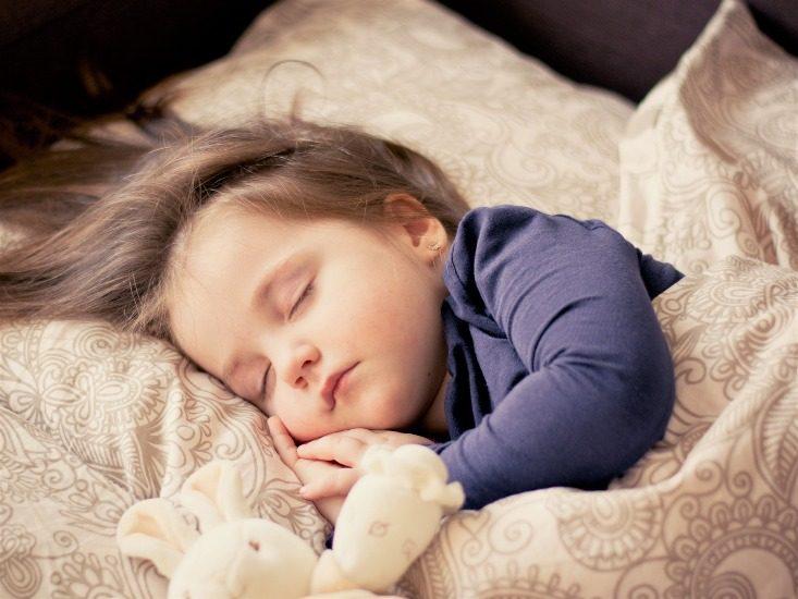 Une fillette dort  avec à ses côtés un toutou en forme de lapin.