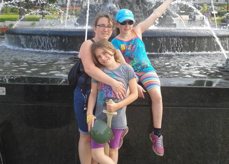 Danielle Savard pose avec ses deux filles devant une fontaine du quartier Hochelaga.