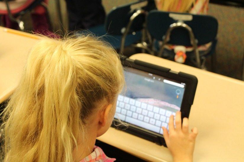 Une fillette blonde écrit sur une tablette numérique.