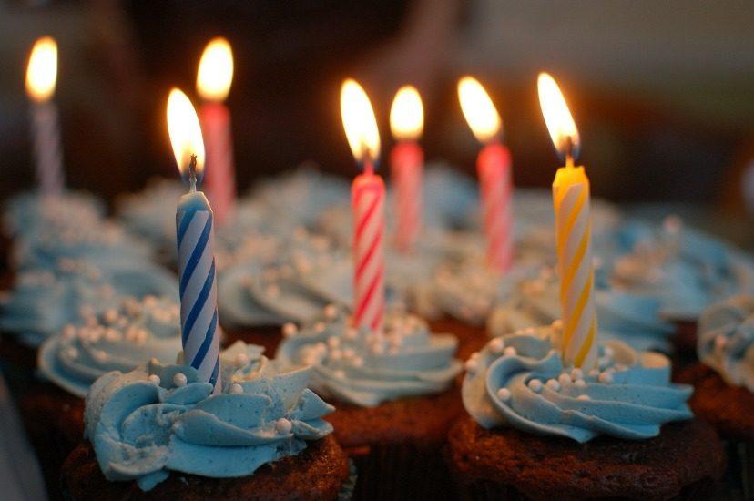 Petits gâteaux avec glaçage et une bougie allumée sur chacun.