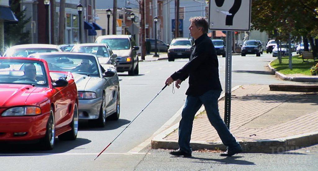 Un homme qui utilise une canne blanche traverse une rue.