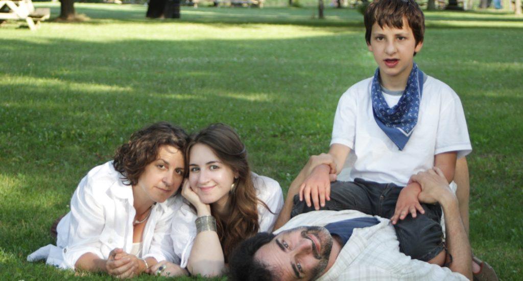 Jean-Paul Eid avec sa compagne et ses enfants. Ils sont tous habillés de blanc et couchés dans l'herbe d'un parc.