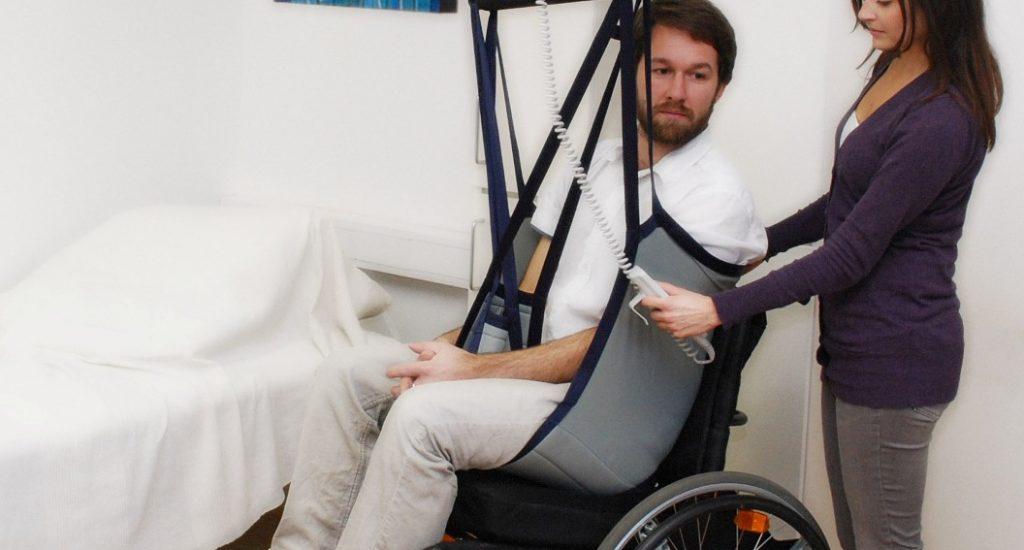 Une préposé transfert un homme de sa chaise à son lit grâce à un lève-personne.