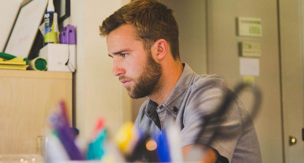 Homme assis à un bureau de travail.