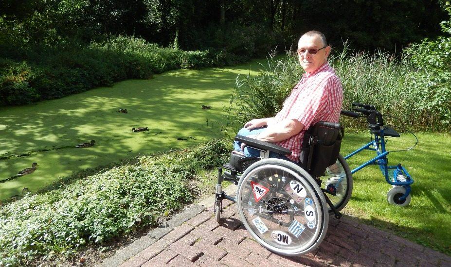 Un homme en fauteuil roulant pose à côté d'un jardin.