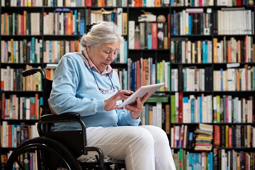 Une dame âgée en fauteuil roulant lit sur une tablette devant un étagère rempli de livres.