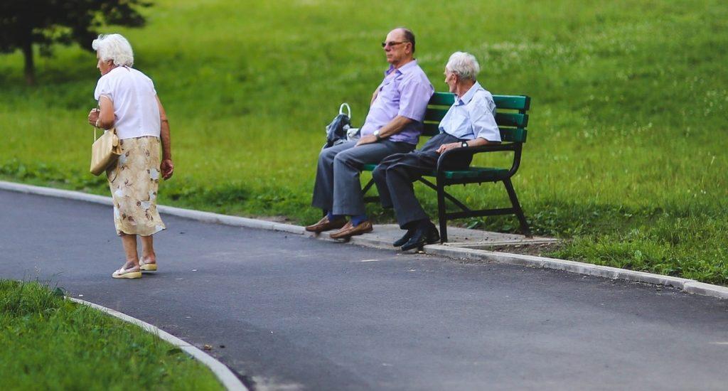 Une femme âgée marche dans un parc. Deux hommes, âgés aussi, sont assis sur un banc.