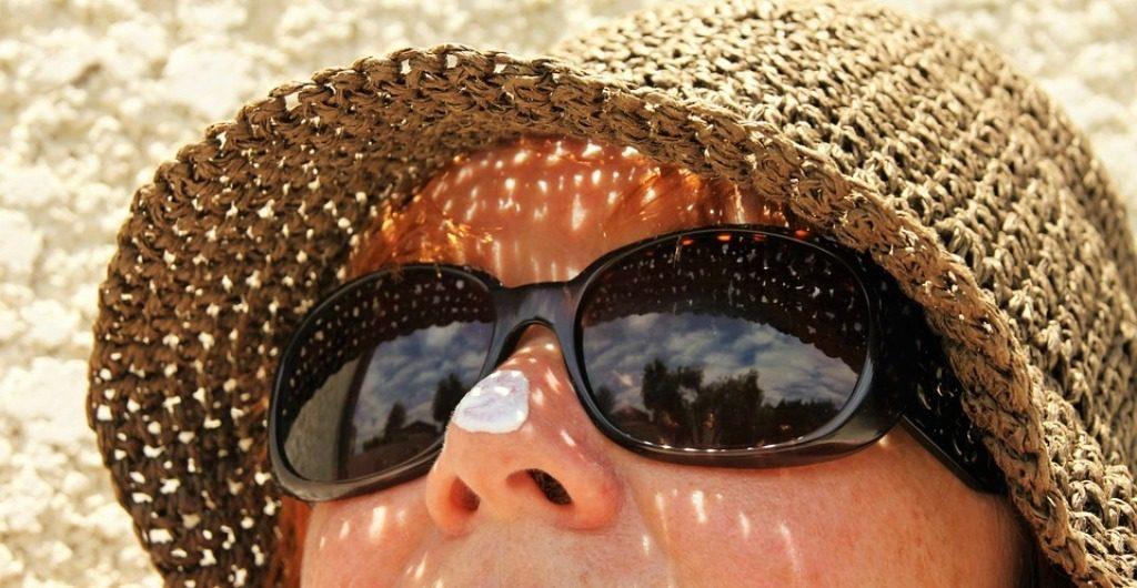 Femme portant des verres fumées et un chapeau de paille.