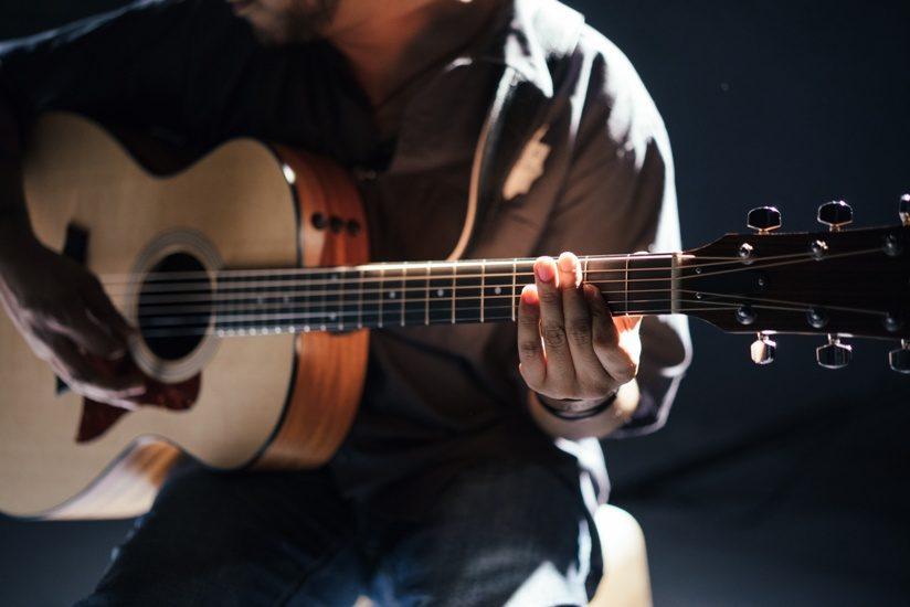 Joueur de guitare. On ne lui voit pas la tête.