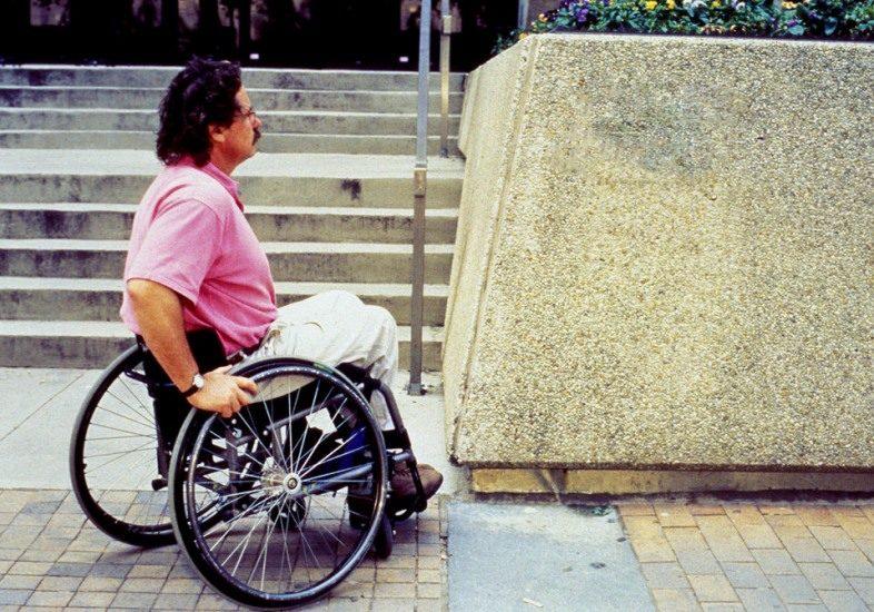Un homme en fauteuil roulant est au pied de l'escalier d'un édifice public.