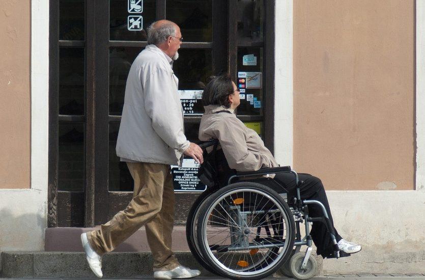 Un homme assez âgé pousse une femme en fauteuil roulant.