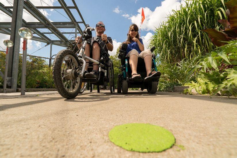 Deux personnes en aides à la mobilité motorisés circulent dans le sentier Kéroul du Jardin Botanique