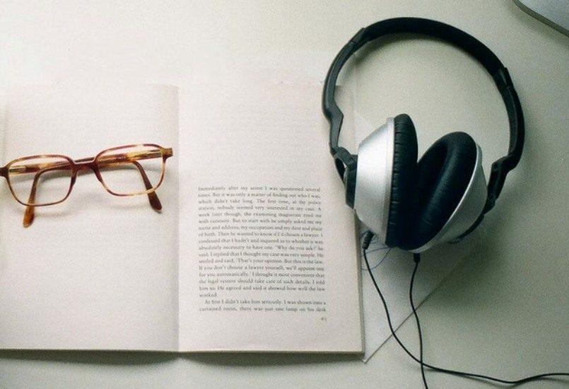 Un livre avec à côté des écouteurs.